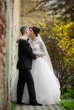 Jeunes mariés embrassant et étreignant près de la vieille fin de mur de bâtiment Photographie stock libre de droits