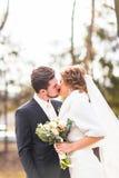 Jeunes mariés embrassant leur jour du mariage dehors photographie stock