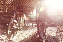 Jeunes mariés embrassant près du chariot en bois Images libres de droits