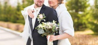 Jeunes mariés embrassant sur leur plan rapproché de jour du mariage Photos stock