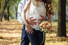 Jeunes mariés enceintes heureux tenant le bouquet de mariage Photographie stock libre de droits