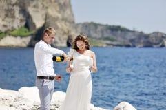 Jeunes mariés faisant le pain grillé avec le champagne près de la mer, Naples, Italie Photo stock