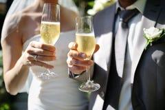Jeunes mariés faisant un pain grillé avec le champagne Photographie stock libre de droits
