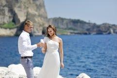 Jeunes mariés faisant un pain grillé avec le champagne près de la mer, Naples, Italie Photo stock