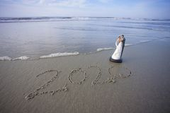 Jeunes mariés Figurine à la plage avec l'année 2020 écrite dans le sable Images stock