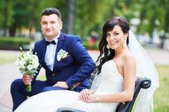 Jeunes mariés gais avec le bouquet de fleur dehors Photos libres de droits