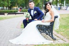 Jeunes mariés gais avec le bouquet de fleur dehors Photographie stock libre de droits