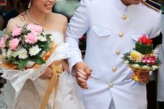 Jeunes mariés gais tenant des mains dans la cérémonie de mariage traditionnelle thaïlandaise Centre sélectif et profondeur de cha Images stock