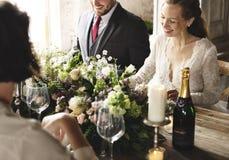 Jeunes mariés Having Meal avec des amis à la réception de mariage Photo stock