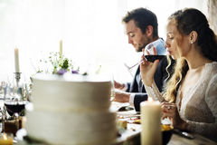 Jeunes mariés Having Meal avec des amis à la réception de mariage Photographie stock libre de droits