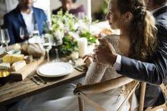 Jeunes mariés Having Meal avec des amis à la réception de mariage Photos stock