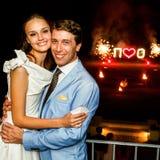 Jeunes mariés heureux étreignant le sourire sur le feu d'artifice de fond Photo stock