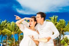 Jeunes mariés heureux ayant l'amusement sur la plage tropicale mariage photographie stock
