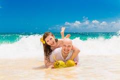 Jeunes mariés heureux ayant l'amusement sur une plage tropicale Épouser Image libre de droits
