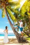 Jeunes mariés heureux ayant l'amusement sur une plage tropicale sous la paume Photo stock