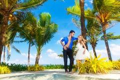 Jeunes mariés heureux ayant l'amusement sur une plage tropicale sous le p Photographie stock