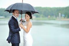 Jeunes mariés heureux dans un jour du mariage pluvieux Images libres de droits