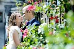 Jeunes mariés heureux de couples près des fleurs et des plantes dans le jour du mariage Photos stock