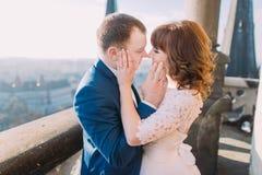 Jeunes mariés heureux de nouveaux mariés embrassant sur le balcon de la vieille cathédrale gothique Images stock
