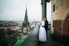Jeunes mariés heureux de nouveaux mariés se tenant sur le balcon de la vieille cathédrale gothique Photographie stock libre de droits
