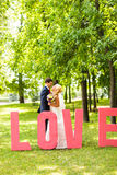 Jeunes mariés heureux embrassant près d'une lettre l'amour de mot Photos libres de droits