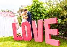 Jeunes mariés heureux embrassant près d'une lettre l'amour de mot Photographie stock libre de droits