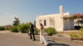 Jeunes mariés heureux le jour du mariage marchant à l'arrière-plan de l'hôtel clips vidéos
