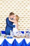 Jeunes mariés heureux magnifiques élégants embrassant à la réception de mariage, moment gai émotif images stock