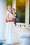 Jeunes mariés heureux près du fléau blanc images stock