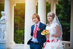 Jeunes mariés heureux près du fléau blanc photos stock