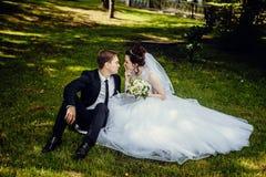 Jeunes mariés heureux reposer l'été sur l'herbe en parc et s'amuser photos libres de droits