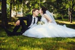 Jeunes mariés heureux reposer l'été sur l'herbe en parc et s'amuser image libre de droits