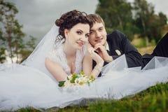 Jeunes mariés heureux reposer l'été sur l'herbe en parc et s'amuser images libres de droits