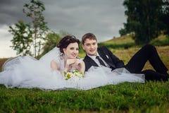 Jeunes mariés heureux reposer l'été sur l'herbe en parc et s'amuser image stock