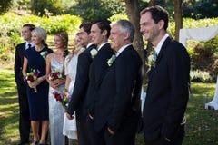 Jeunes mariés heureux se tenant avec des invités images libres de droits