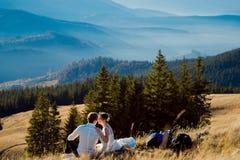 Jeunes mariés heureux souriant entre eux se reposant sur la crête de montagne Lune de miel dans les Alpes Image stock