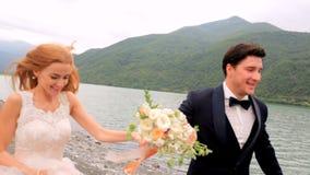 Jeunes mariés heureux sur la course de jour du mariage le long de la berge à l'arrière-plan de belles montagnes georgia banque de vidéos