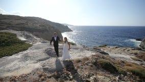 Jeunes mariés heureux sur le bord de la mer leur jour du mariage Mouvement lent banque de vidéos
