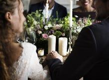 Jeunes mariés Holding Hands Each autre sur la réception de mariage Image stock