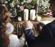 Jeunes mariés Holding Hands Each autre sur la réception de mariage Photos stock