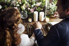 Jeunes mariés Holding Hands Each autre sur la réception de mariage Photo libre de droits