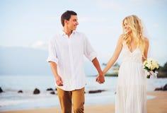 Jeunes mariés, ménage marié nouvellement romantique tenant des mains Wal Photographie stock
