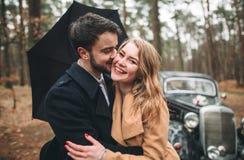 Jeunes mariés magnifiques de nouveaux mariés posant dans la forêt de pin près de la rétro voiture dans leur jour du mariage Photos libres de droits