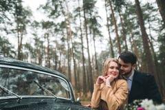 Jeunes mariés magnifiques de nouveaux mariés posant dans la forêt de pin près de la rétro voiture dans leur jour du mariage Photo libre de droits