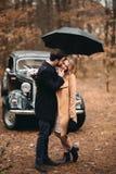 Jeunes mariés magnifiques de nouveaux mariés posant dans la forêt de pin près de la rétro voiture dans leur jour du mariage Photos stock