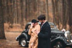 Jeunes mariés magnifiques de nouveaux mariés posant dans la forêt de pin près de la rétro voiture dans leur jour du mariage Photographie stock