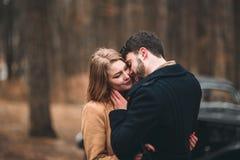 Jeunes mariés magnifiques de nouveaux mariés posant dans la forêt de pin près de la rétro voiture dans leur jour du mariage Image stock