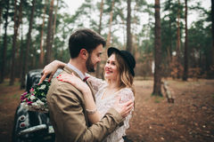 Jeunes mariés magnifiques de nouveaux mariés posant dans la forêt de pin près de la rétro voiture dans leur jour du mariage Photo stock
