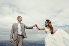 Jeunes mariés magnifiques tenant des mains et dansant au ciel et au Cl Image libre de droits