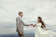 Jeunes mariés magnifiques tenant des mains et dansant au ciel et au Cl Photographie stock